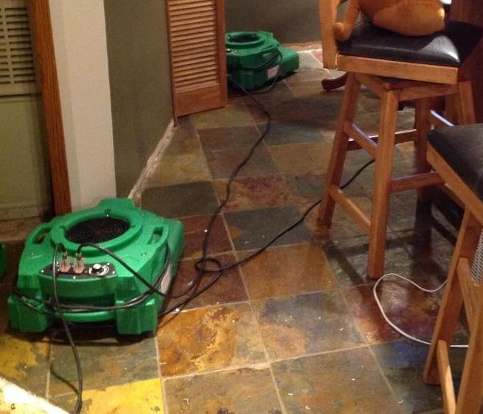 Green air movers set up and running against two walls.