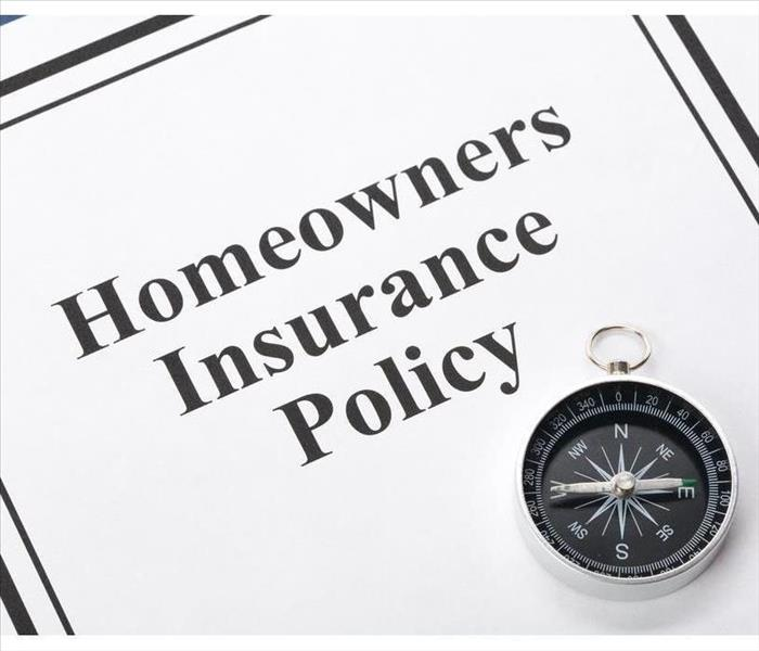 A sheet that says Homeowners Insurance Policy and there is a compass on the sheet